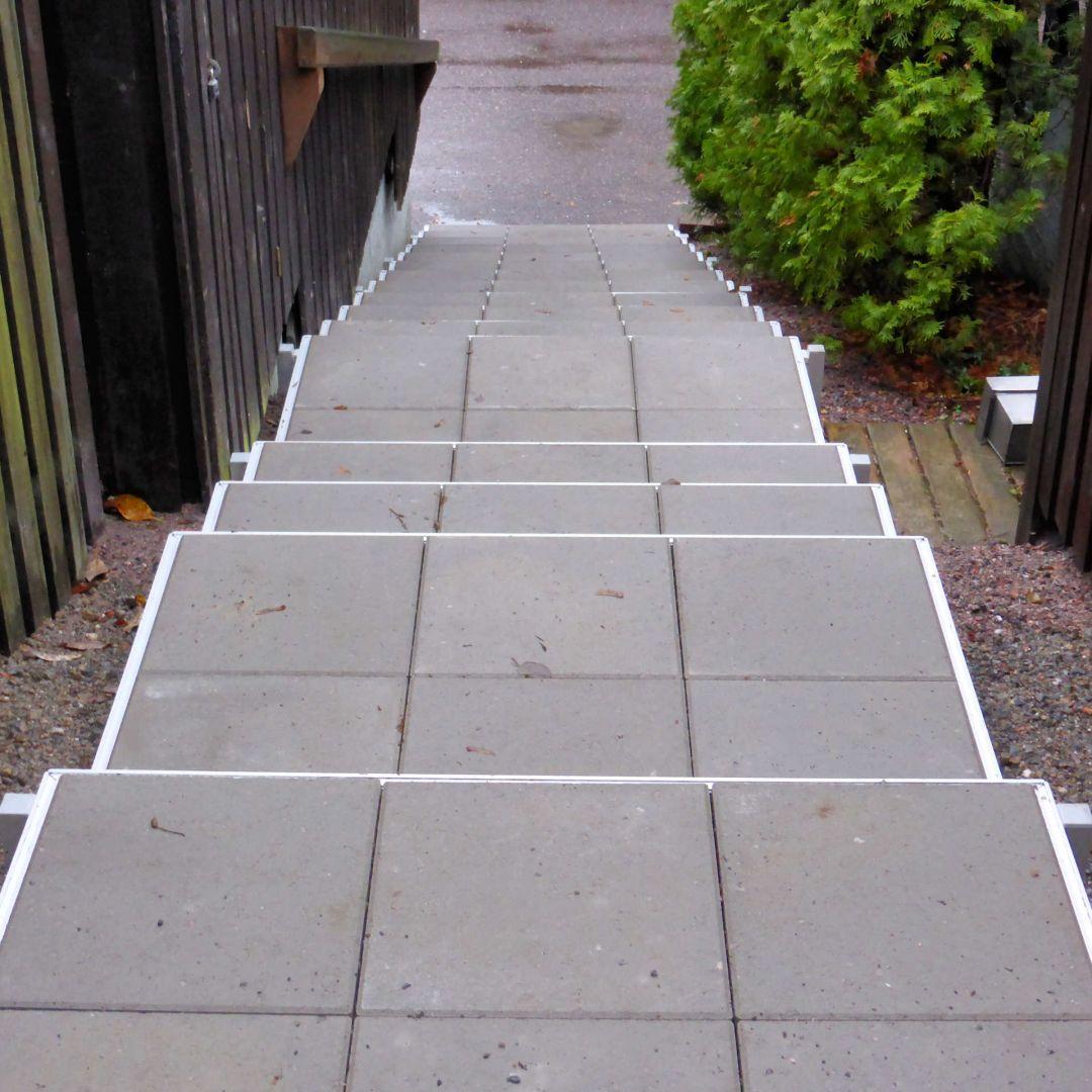 Alukehysportaat (ulkoportaat) jossa Siperian lehtikuusi käsijohteet ja välitasoja. Leveys 125 cm, askelman syvyys 40 cm. Kate sileitä betonilaattoja. Kuva ylhäältä.