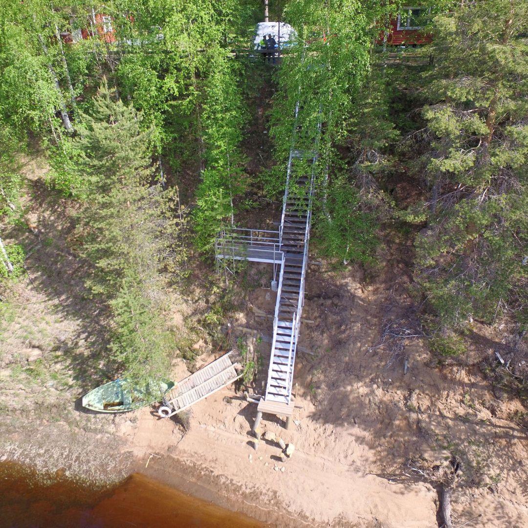 Säätöportaat (ulkoportaat) saunalta rantaan. Jyrkkyys n. 42 astetta. Askelmat ovat Siperian lehtikuusta. Kaiteet kummallakin puolella. Alimpana alumiiniset teleskooppiportaat. Oleskelutaso. Kuva ylhäältä.