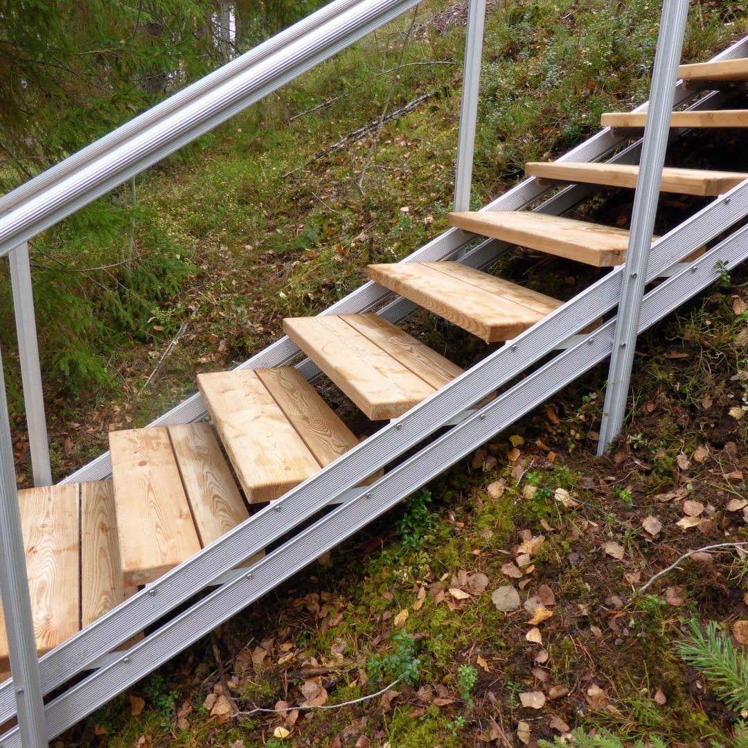 Säätöportaat (ulkoportaat)metsäisellä kalliorinteellä. Askelmat ovat Siperian lehtikuusta. Kuva sivulta.