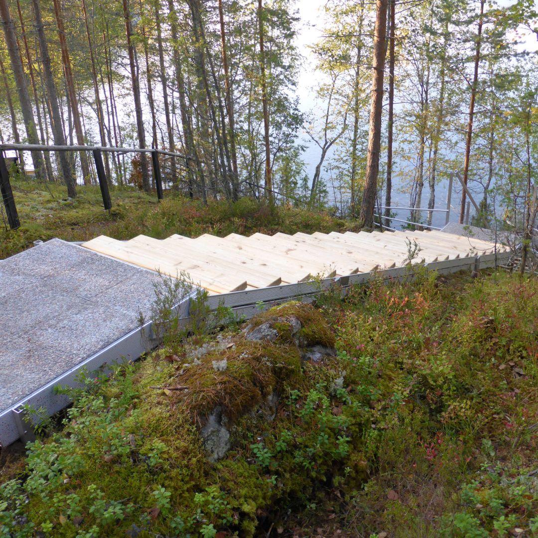 Pitkät, 3-osaiset säätöportaat (ulkoportaat) metsäisellä kalliorinteellä. Kuvassa ylätaso, välitaso ja portaan ylin osa. Askelmat ovat Siperian lehtikuusta. Kuva ylhäältä.
