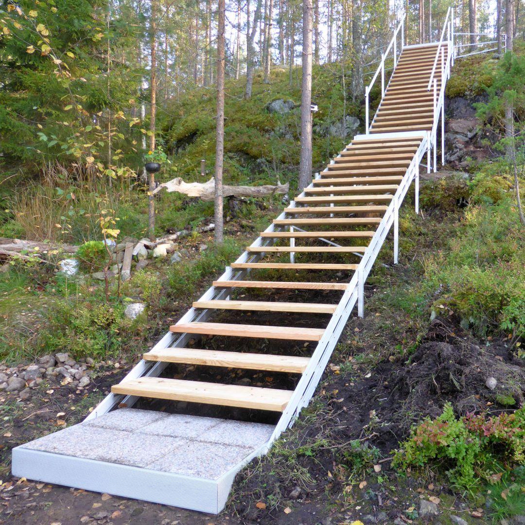 Pitkät, 3-osaiset säätöportaat (ulkoportaat) metsäisellä kalliorinteellä. Kaksi välitasoa ja alataso. Askelmat ovat Siperian lehtikuusta. Kuva alhaalta.