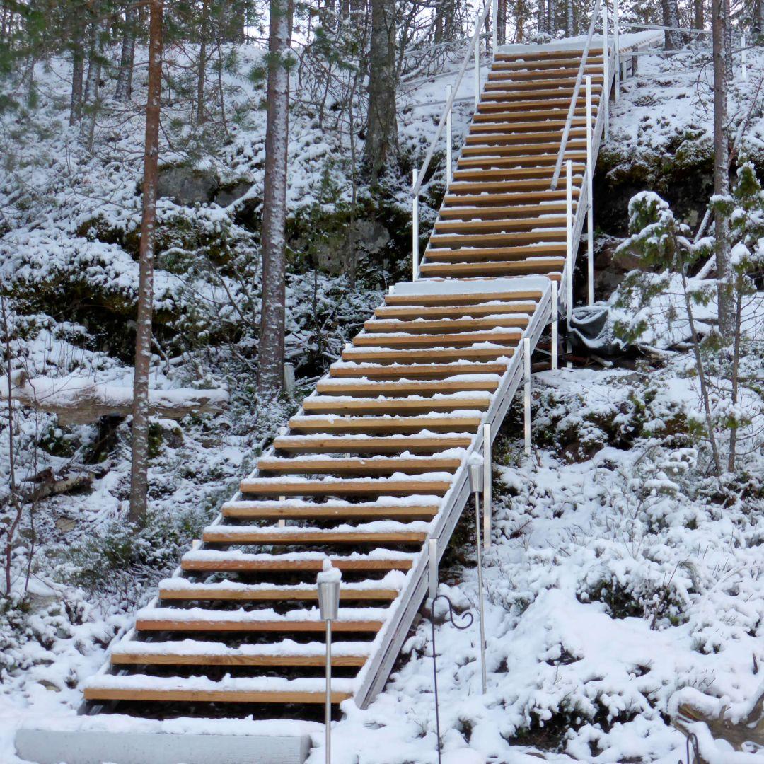 Pitkät, 3-osaiset säätöportaat (ulkoportaat) metsäisellä kalliorinteellä. Kaksi välitasoa ja alataso. Askelmat ovat Siperian lehtikuusta. Kuva alhaalta, talvella.