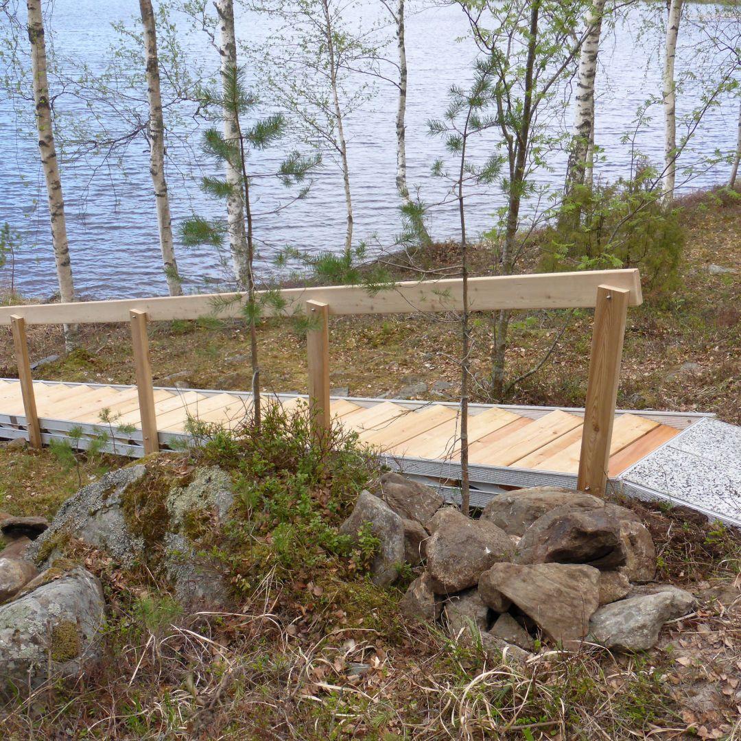 Säätöportaat (ulkoportaat) saunalta laiturille. Askelmat, käsijohde ja kaiteen tolpat ovat Siperian lehtikuusta. Leveys 85 cm. Ylätaso.
