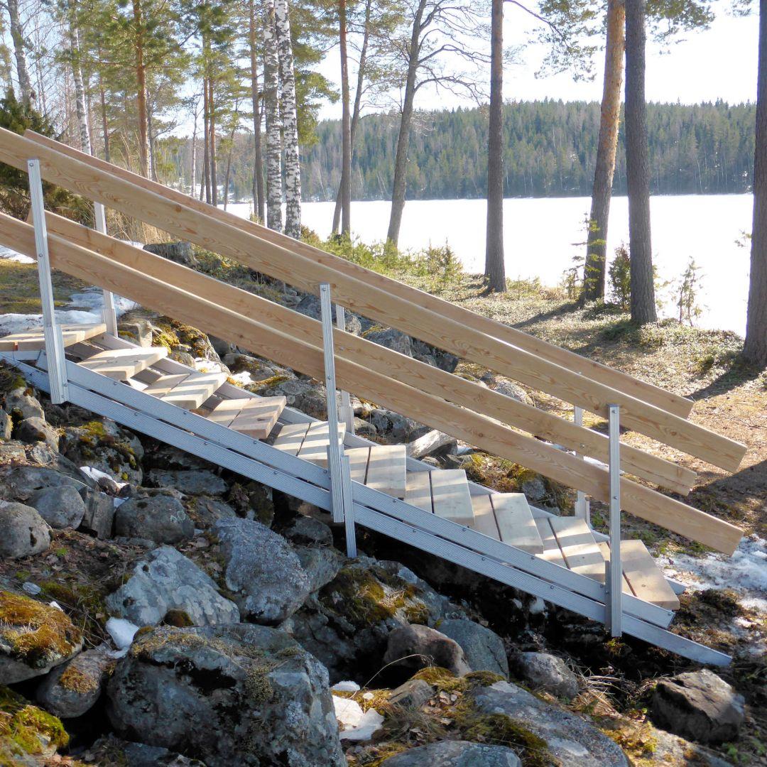 Pienet säätöportaat (ulkoportaat) saunalta rantakaistaleelle. Jykevä avokaide. Askelmat ja käsijohteet ovat Siperian lehtikuusta.