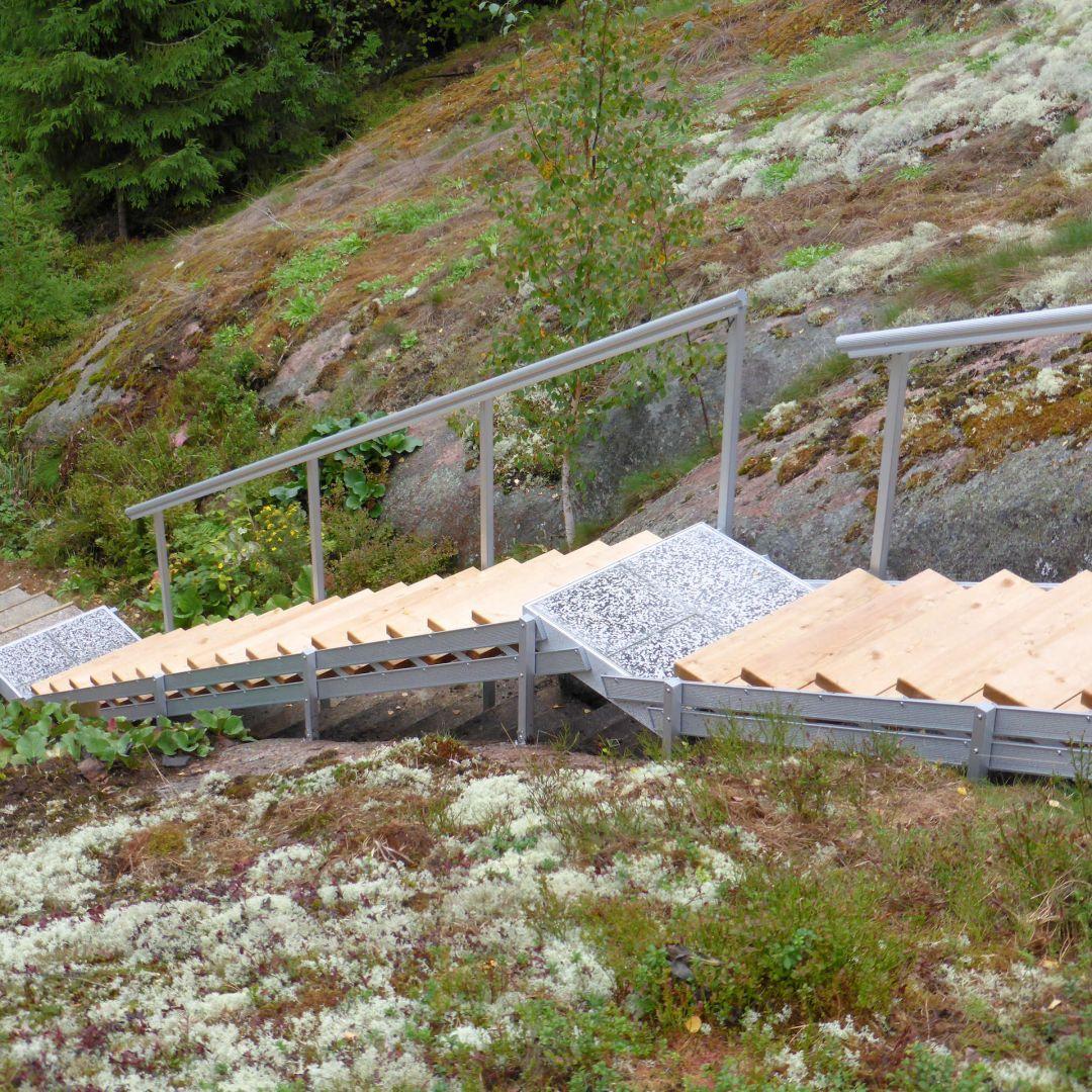 Säätöportaat (ulkoportaat) jyrkällä kalliorinteellä. Välitaso. Puu on Siperian lehtikuusta, leveys 85 cm. AuroraLED valaistus käsijohteen alapinnassa.