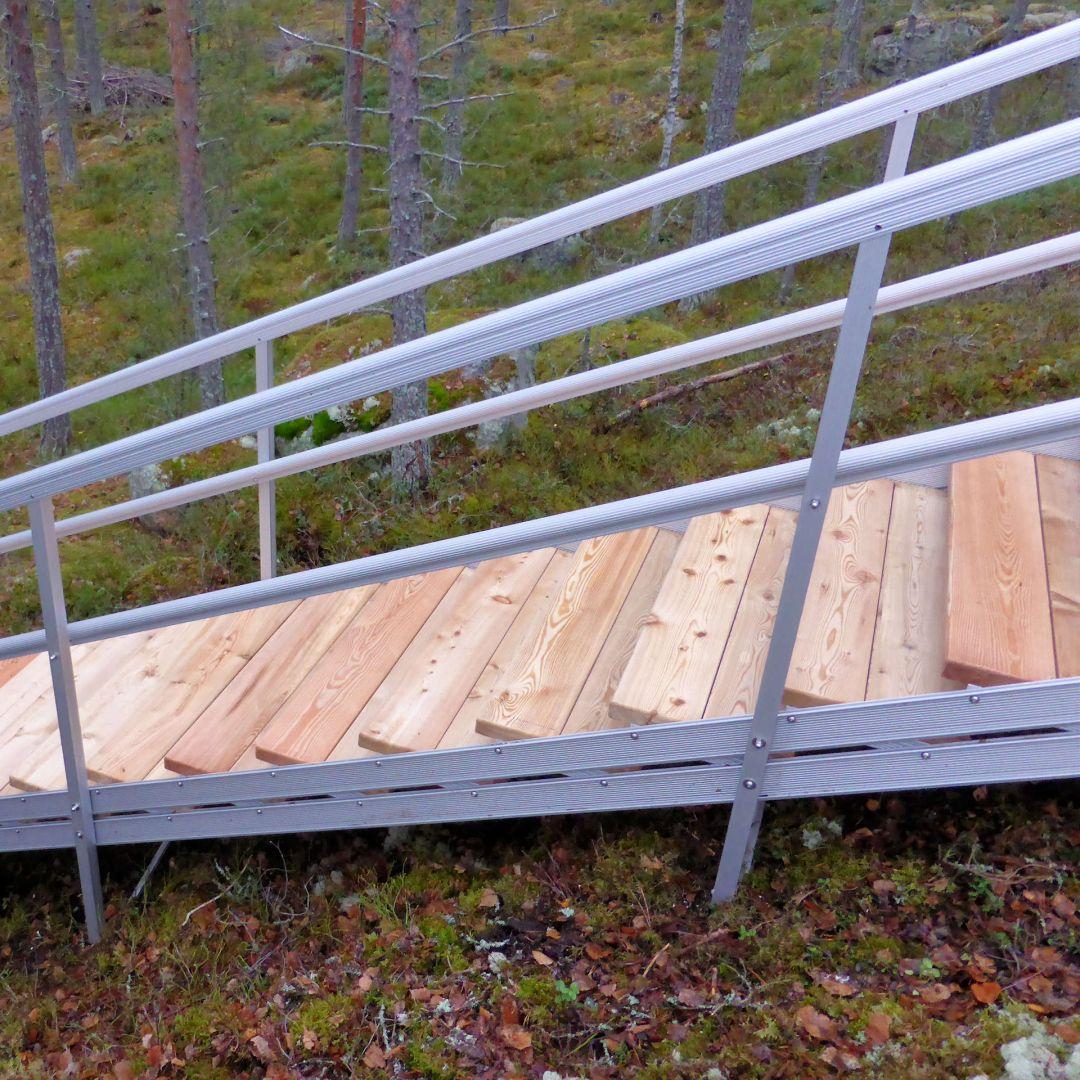 Säätöportaat (ulkoportaat) metsäisellä kalliorinteellä. Askelmat Siperian lehtikuusta, leveys 100 cm.